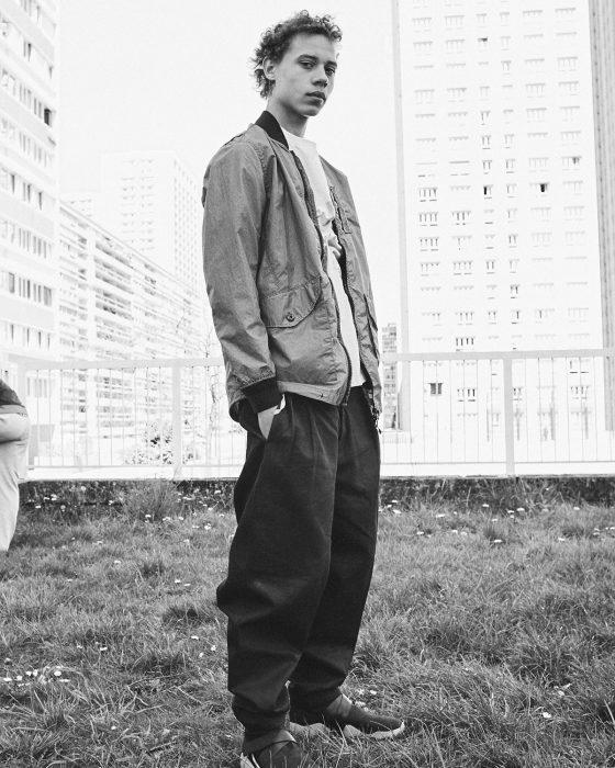 Lye wears jacket Stone Island, t-shirt Kenzo, trousers Hed Mayner.