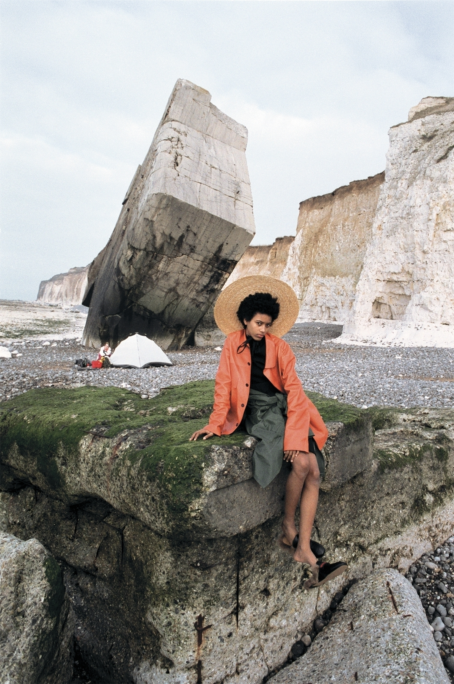 Coat, pleated top & skirt by Jil Sander, parka around the waist from stylist's archive, oversized brimmed hat by Jacquemus, moccasins by Gucci.