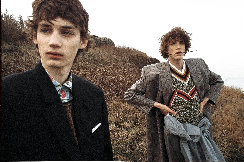 Roberts wears jacket by Balenciaga, shirt & sleeveless pullover by Prada. Harold wears coat by Balenciaga, sleeveless pullover, coat around the waist & trousers by Prada.