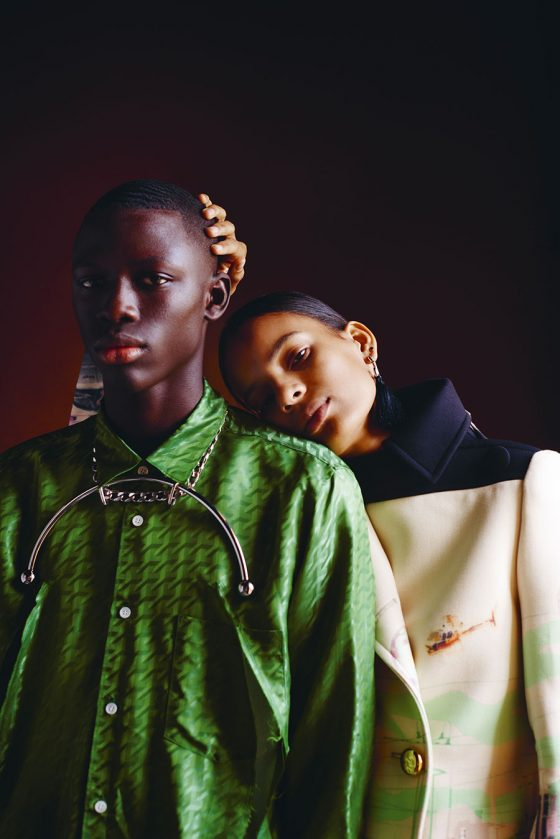 Khadim wears shirt by Comme des Garçons Homme Plus, necklace by Y/Project. Annibelis wears coat by Prada, earrings by Vivenne Westwood