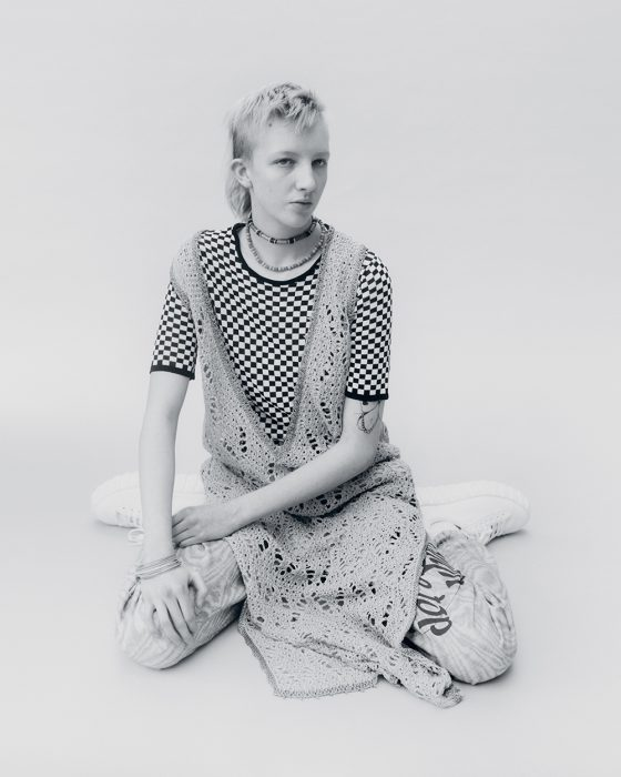 Finn wears dress by JW Anderson, top & jewellery from stylist's archive, trousers Napa by Martine Rose, shoes Eytys