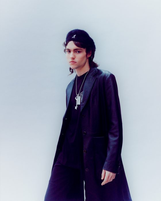 Angus wears coat, trousers & necklace by MM6 Maison Margiela, top by Aries, hat by Kangol